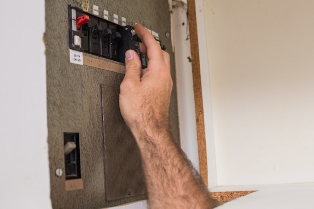 Electrician working on the fuse box