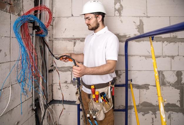 Электрик работает возле доски с проводами. монтаж и подключение электрики.