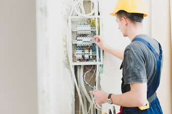 Electrician working with switchboard