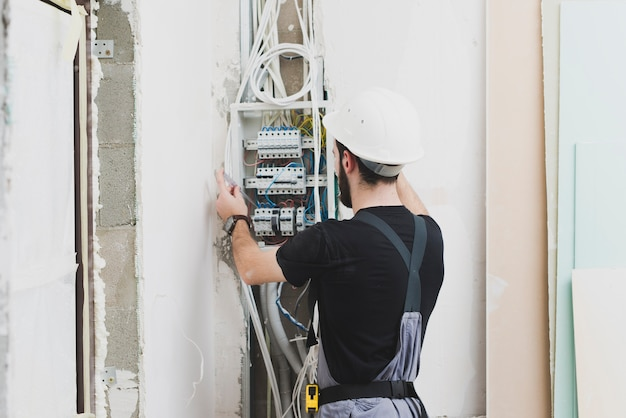 Electrician working with wires in switchboard