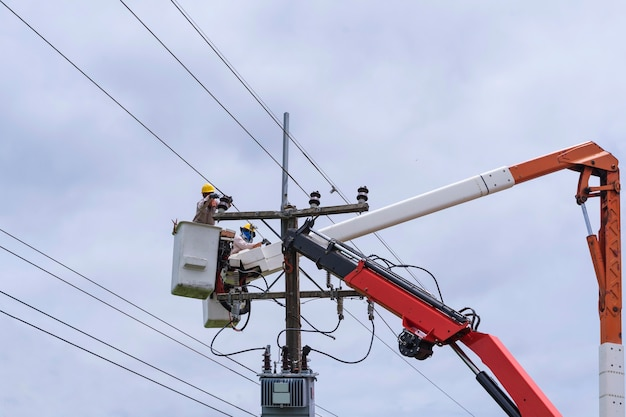 Electrician works on bucket car to maintain high voltage transmission lines.