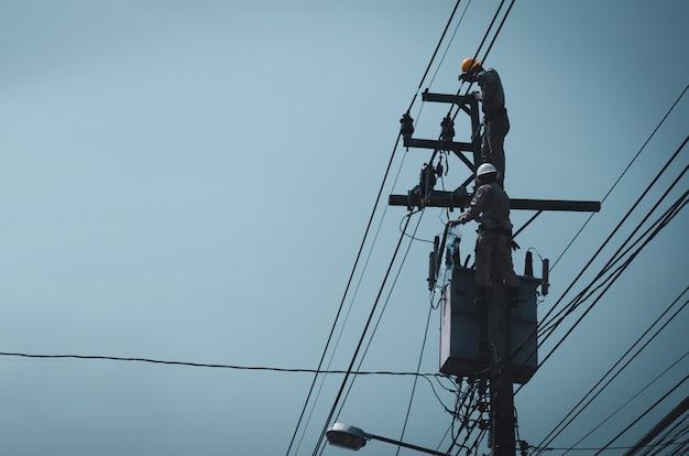 電気技師は、送電線の設置と修理のために電柱に登っています。