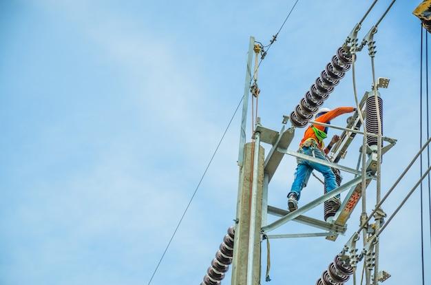 電気技師は、送電線の設置と修理のために電柱に登っています