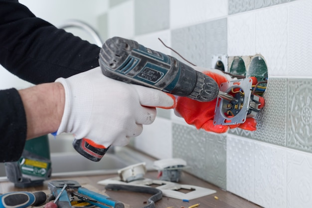 Electricians hand installing outlet on wall with ceramic tiles using professional tools