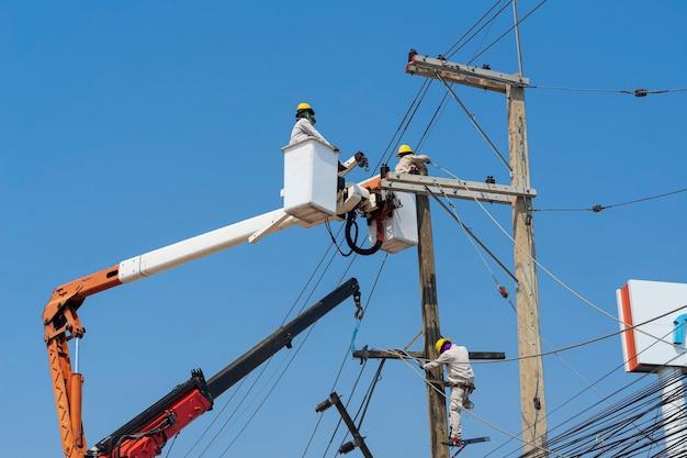 Электрики устанавливают оборудование в высоковольтную сеть.