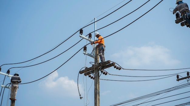 Electricians work on high voltage towers to install new wires and equipment.