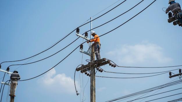 Электрики работают на высоковольтных опорах по установке новых проводов и оборудования.