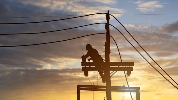 電気技師は、新しい電線や機器を設置するために高電圧タワーに取り組んでいます。