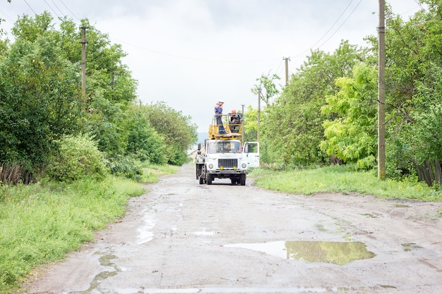 Electricians working on poles, a group of workers in special vehicles