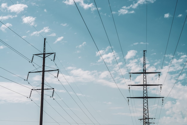 Башня распределения электричества с космосом экземпляра. высоковольтные линии электропередач под облачным небом. минималистичный вид снизу на столбы с проводами в пасмурную погоду.