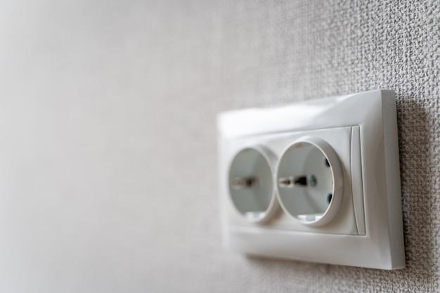 Электрическая розетка в комнате после ремонта с серыми обоями на стене для копирования пространства