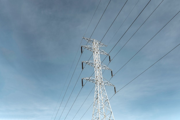 Electricity pole against blue sky clouds, transmission line of electricity to rural, high voltage electricity pole on bright sky clouds background, electricity transmission pylon