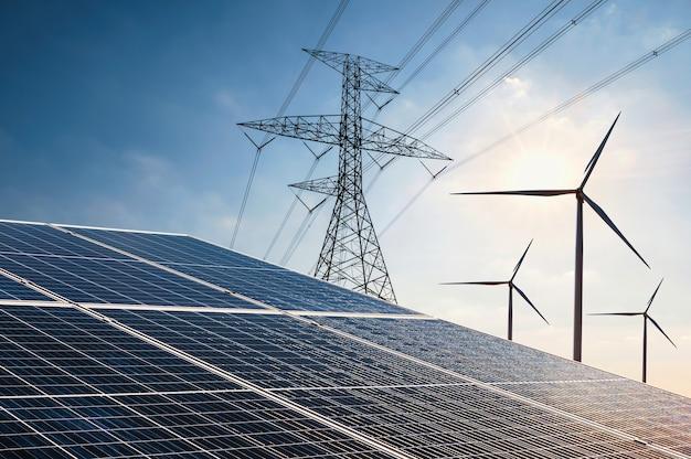 自然界の電力。クリーンエネルギーの概念。タービンとタワーの高電圧を備えたソーラーパネル