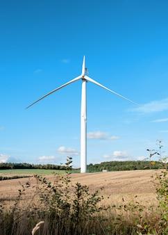 Электроэнергетическая ветряная турбина со сломанной лопастью и поврежденной опорой в ожидании ремонта после аварии.