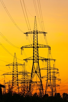 Пилоны электричества против оранжевого и желтого заката