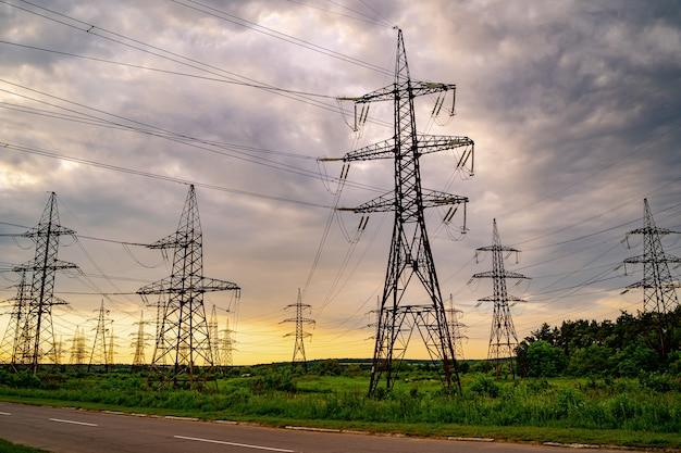 녹색 잔디에 전기 철탑과 고압 전력선. 발전소. 전력망. 아래에서 볼 수 있습니다.
