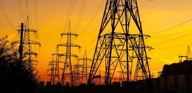 일몰 동안 시골 풍경을 가로 질러 전원을 공급하는 전기 철탑 프리미엄 사진