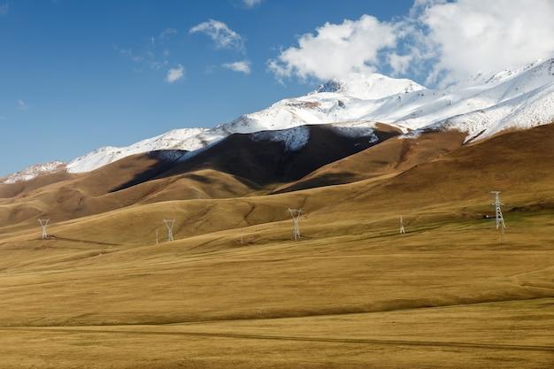 雪に覆われた山々を走る電気の鉄塔。キルギスタンの山々。