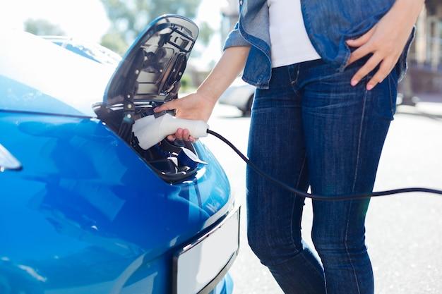 전기 공급. 그녀의 차 근처에 서서 그것을 사용하는 동안 전기 충전기를 들고 잘 생긴 숙련 된 여성 운전자