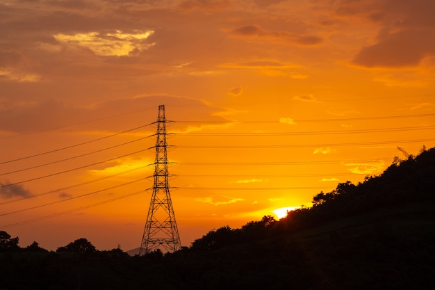 Electricity transmission power lines at sunset, high voltage tower.