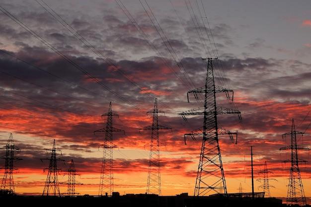 일몰 시 전기 전송 철탑 및 전력선