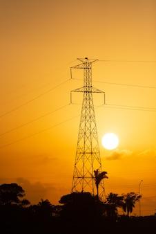 夕日を背景にした送電鉄塔
