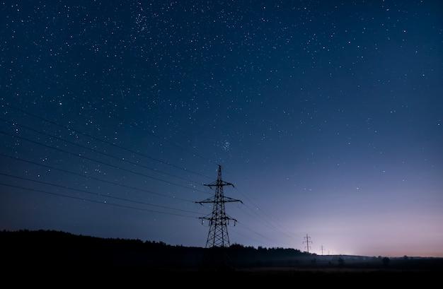 Башни передачи электроэнергии с пылающими проводами на фоне звездного неба.