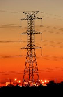 늦은 오후 주황색 하늘이 있는 전화 타워