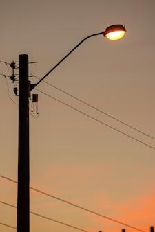 주황색 일몰 하늘을 배경으로 짜릿한 게시물입니다.