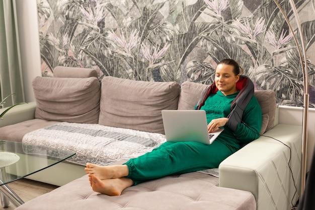 Электромассажер и подушка для домашнего или автомобильного массажа плеч и шеи женщины, получающей массаж во время работы на ноутбуке. расслабляющий массаж, концепция здоровья домашнего устройства