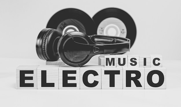 Electro music inscription on wooden cubes and vinyl records and headphones