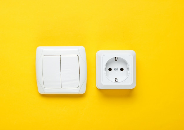 Электророзетка, выключатель на желтой стене, минимализм