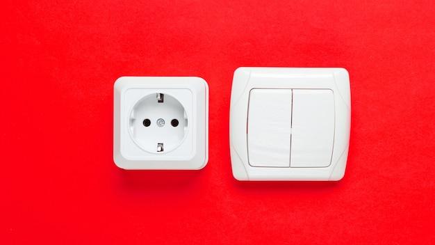 Электро розетка, выключатель на красном фоне стены, минимализм