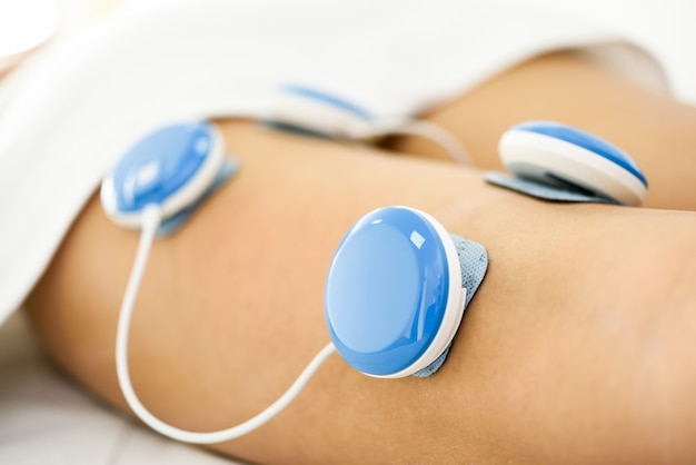 Electro stimulation in physical therapy to a young woman leg.
