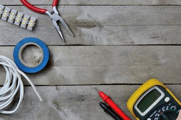 木製の背景にエレクトロ ツールとテスター。コピースペース