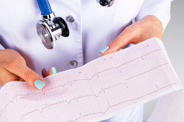 Электрокардиограмма, экг в руке женщины-врача. медицинское обслуживание. клиника кардиология сердечный ритм и крупный план теста пульса. распечатка кардиограммы.