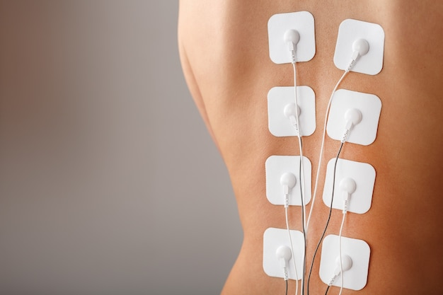 Electrode stimulating massage of the spine at home. medical procedure for muscle tone and beauty