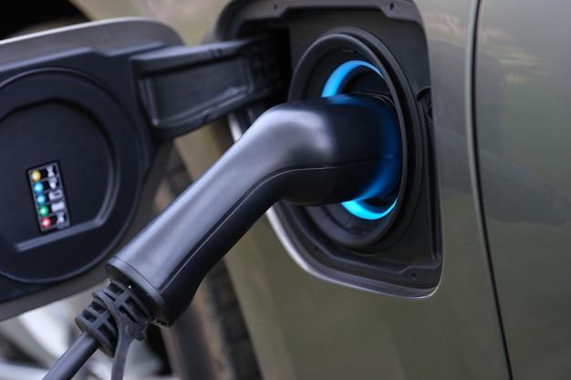 Электромобильная зарядная вилка вставляется в зарядную розетку автомобиля.