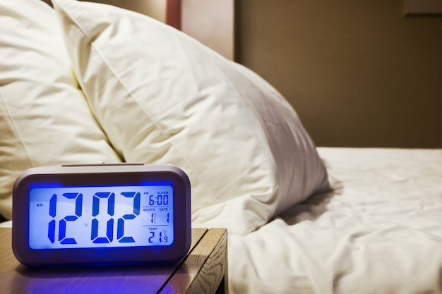 Electronic alarm clock stands on a bedside table in the room
