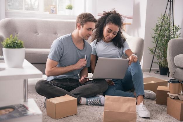 電子バンキングサービス。彼らの購入の支払い中にクレジットカードを使用してうれしそうなポジティブなカップル