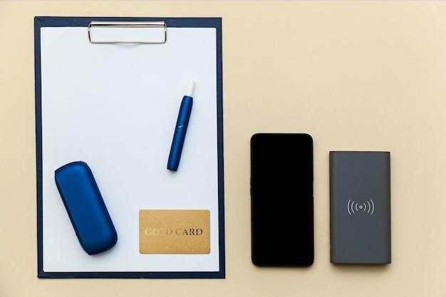 電子ブルーiqosタバコ、電話、パワーバンク、ベージュの背景にクリップペーパーa4が付いたフォルダー。テキスト、ロゴ、デザインの場所が記載された写真。コンセプトオフィス。