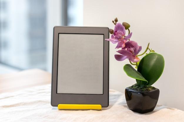 テーブルの上の人工ピンクの蘭の横に空白の画面を持つ電子書籍