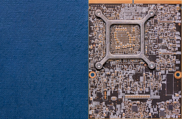 Electronic circuit board on blue background with copy space, top view, close up