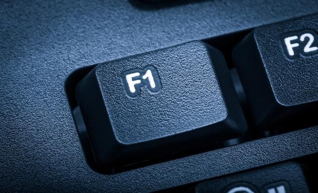 Электронная коллекция - деталь черной компьютерной клавиатуры. акцент на клавишу f1. тонировка синяя.