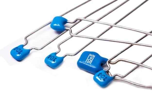 Электронные компоненты: группа керамических конденсаторов низкого напряжения на белом фоне