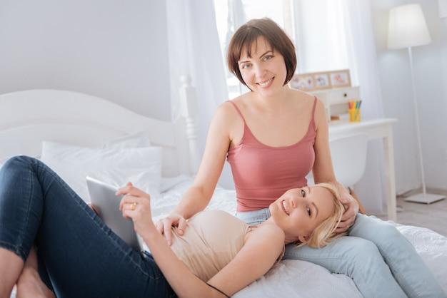 電子機器。ベッドに横になって、彼女のガールフレンドと一緒にいる間タブレットを持っている素敵なポジティブな魅力的な女性