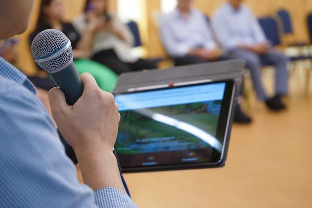 Электронное устройство на азиатской руке играет в социальных сетях в конференц-зале с размытыми людьми позади
