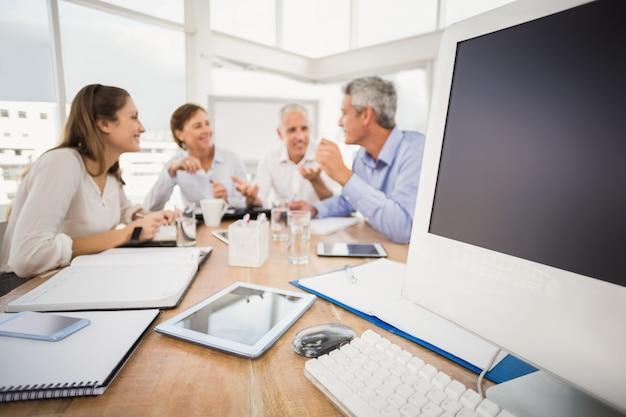 話すビジネスの人々の前にある電子デバイス