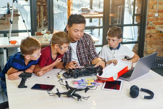 現代の学校の実験室で作業し、電気自動車のモデルをテストするヨーロッパの学童を持つ電子エンジニア