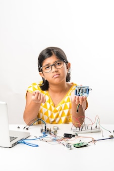 Электронный эксперимент - азиатская индийская маленькая девочка-студентка занимается или изучает науку с помощью проводов, соединений, учится с ноутбука или планшета.